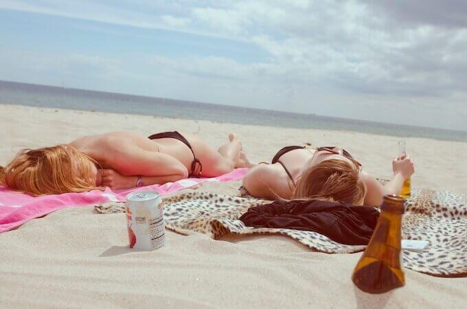海岸で日焼けする女子