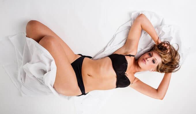 ベッドの上で寝る女性