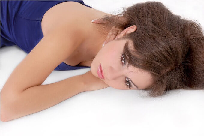 ベッドで寝転ぶ女性